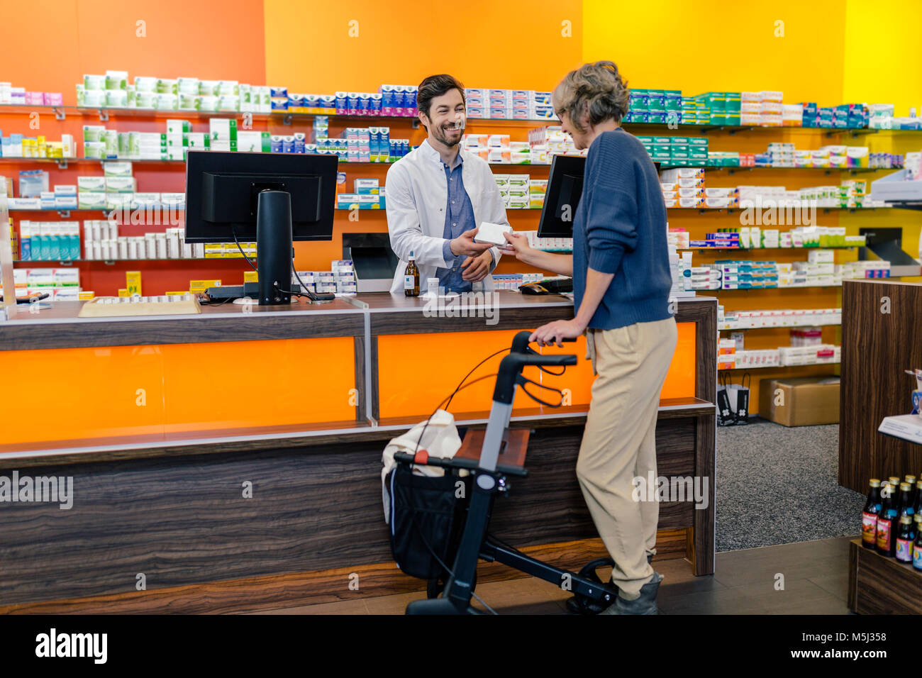 Pharmacist giving medicine to customer with wheeled walker in pharmacy - Stock Image