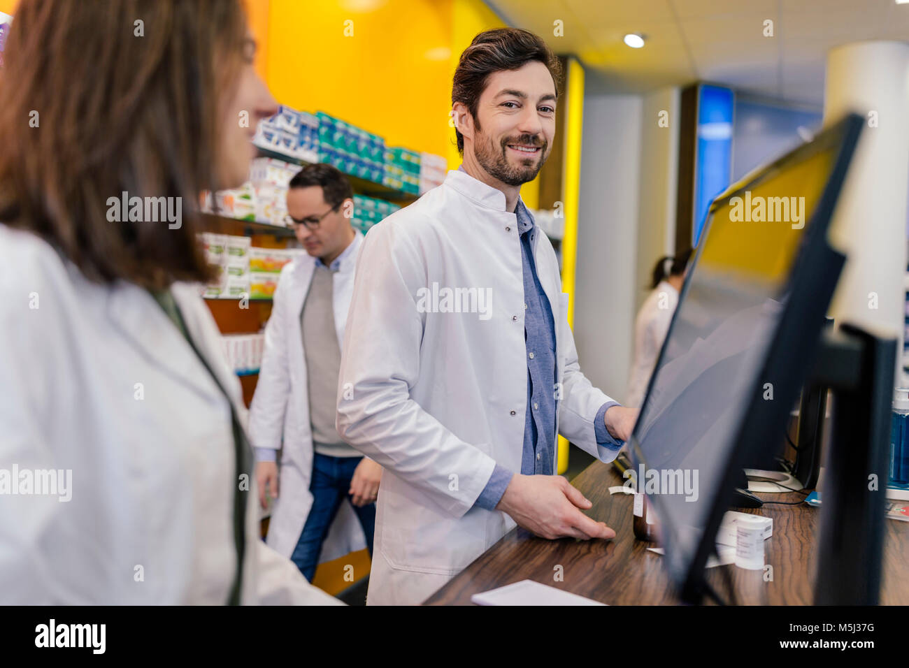 Portrait of smiling pharmacist with colleagues at counter in pharmacy - Stock Image