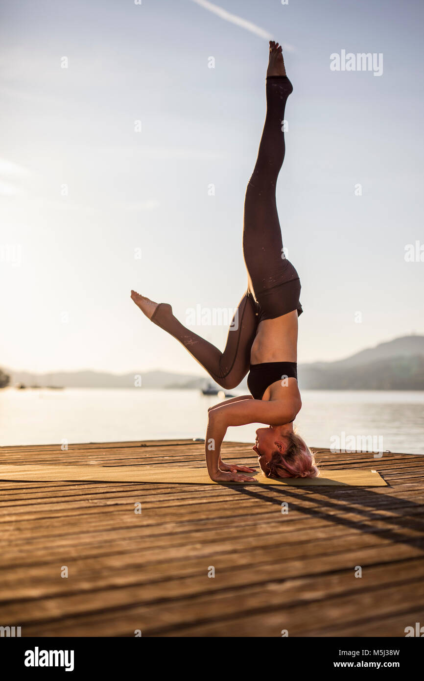 Woman practicing yoga on jetty at a lake doing a headstand - Stock Image