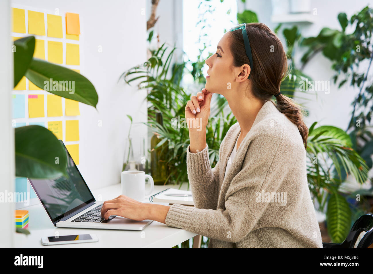Young woman with laptop on desk looking at adhesive notes on the wall - Stock Image
