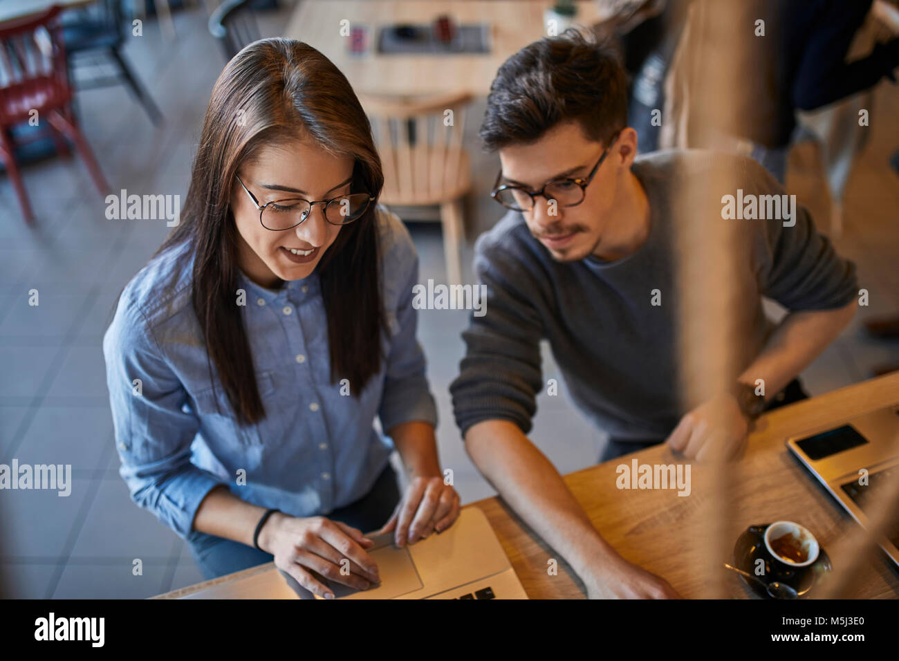 Young woman and man in a cafe with laptop - Stock Image