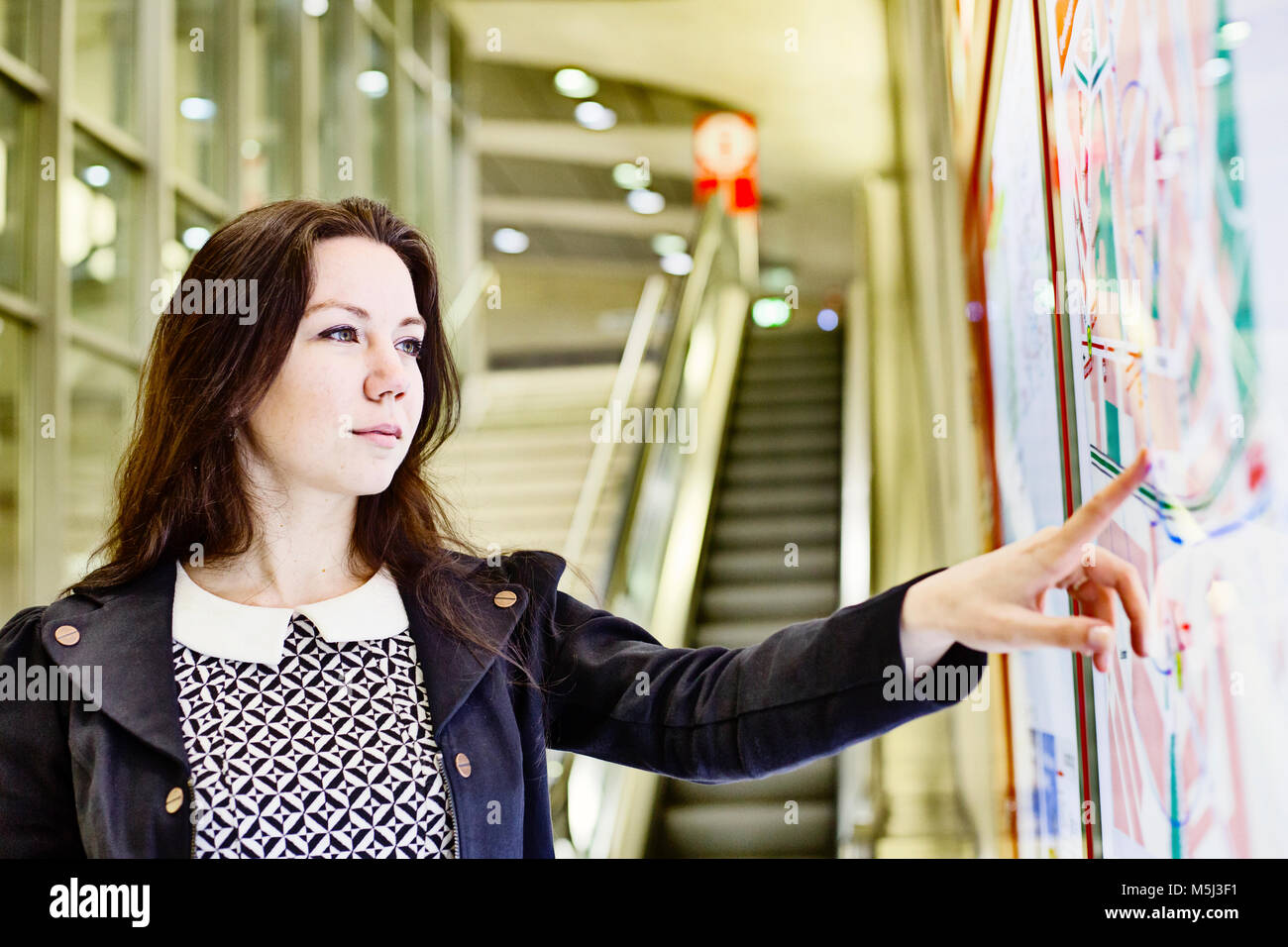 Portrait of young woman looking at city map in underground station - Stock Image