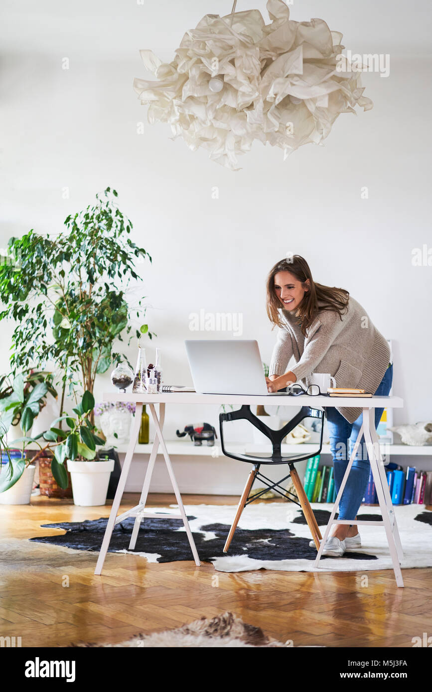 Smiling young woman at home using laptop on desk Stock Photo