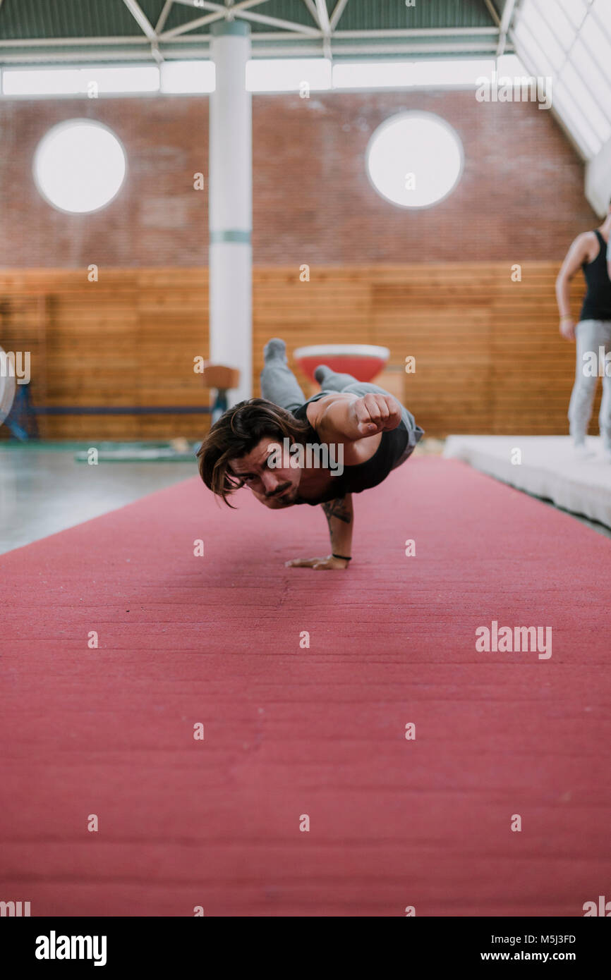 Young man doing acrobatic exercise in gym - Stock Image