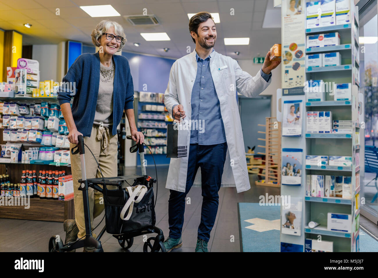 Smiling pharmacist and customer with wheeled walker in pharmacy - Stock Image