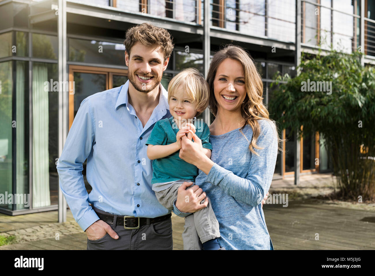 Portrait of smiling parents with son in front of their home - Stock Image