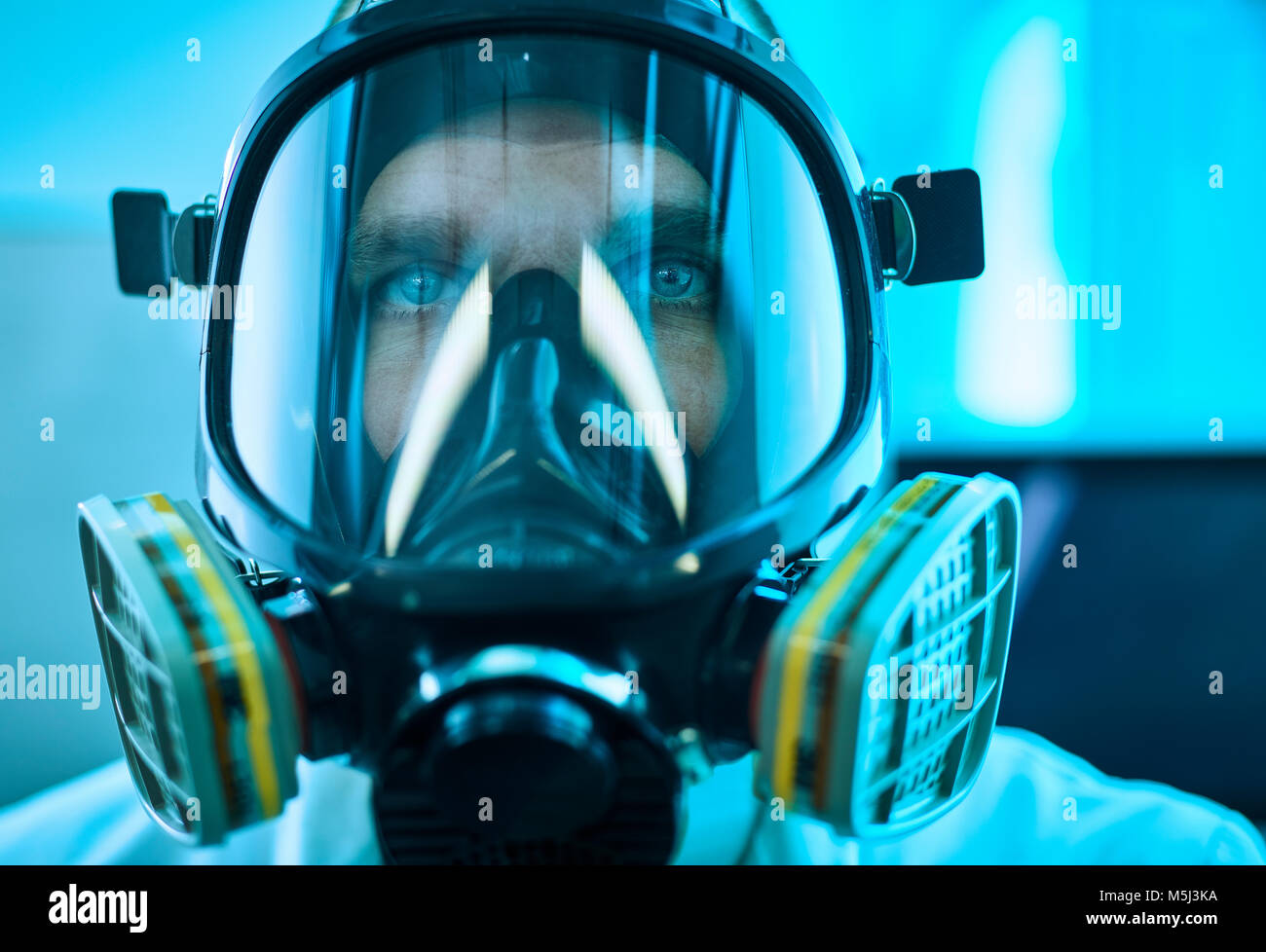 Portrait of man wearing respirator - Stock Image