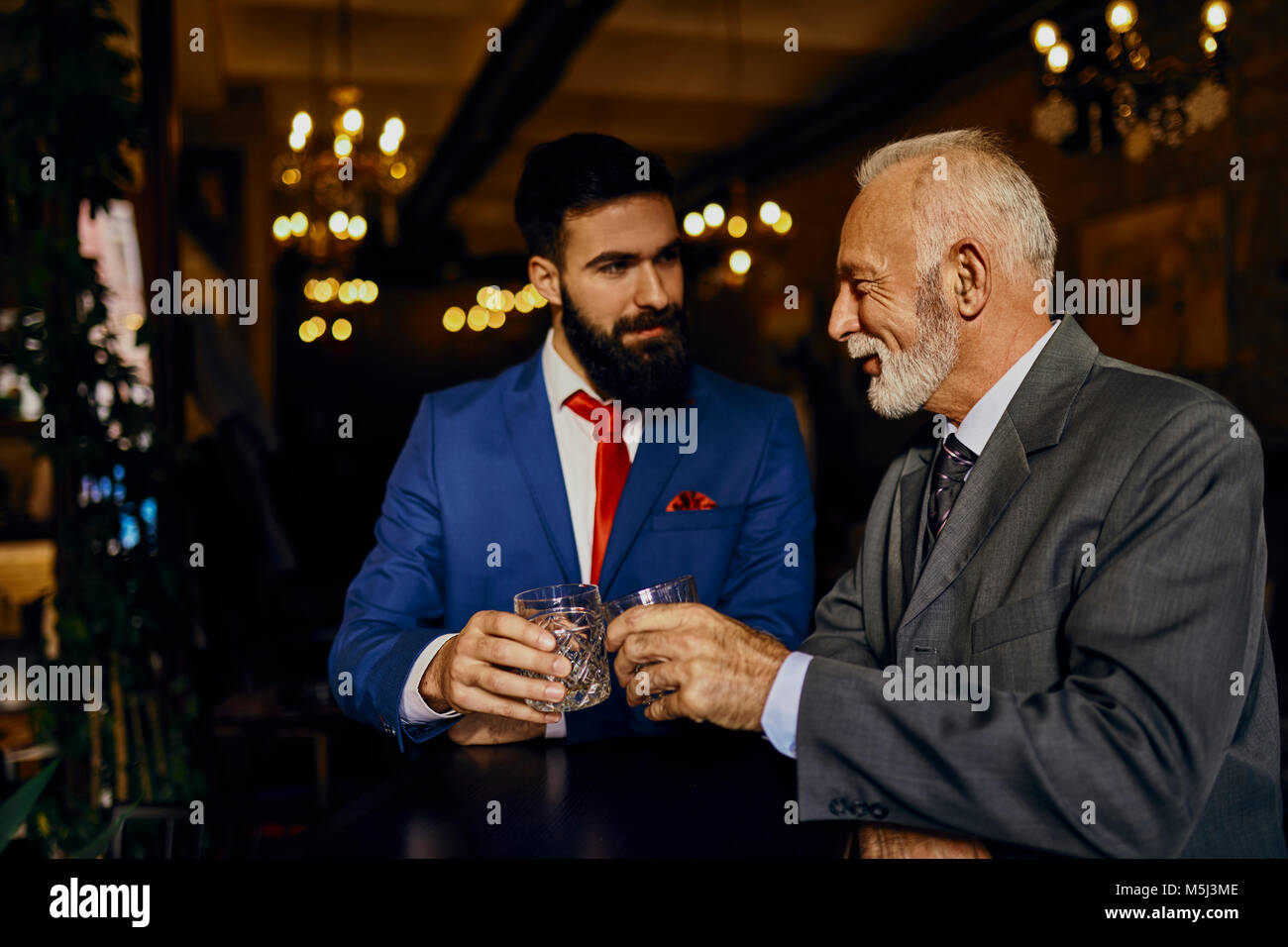 Two elegant men in a bar clinking tumblers - Stock Image