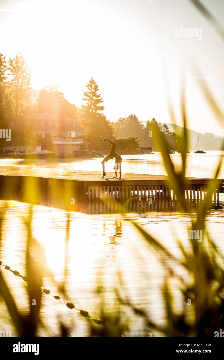 Woman practicing yoga on jetty at a lake doing a handstand - Stock Image