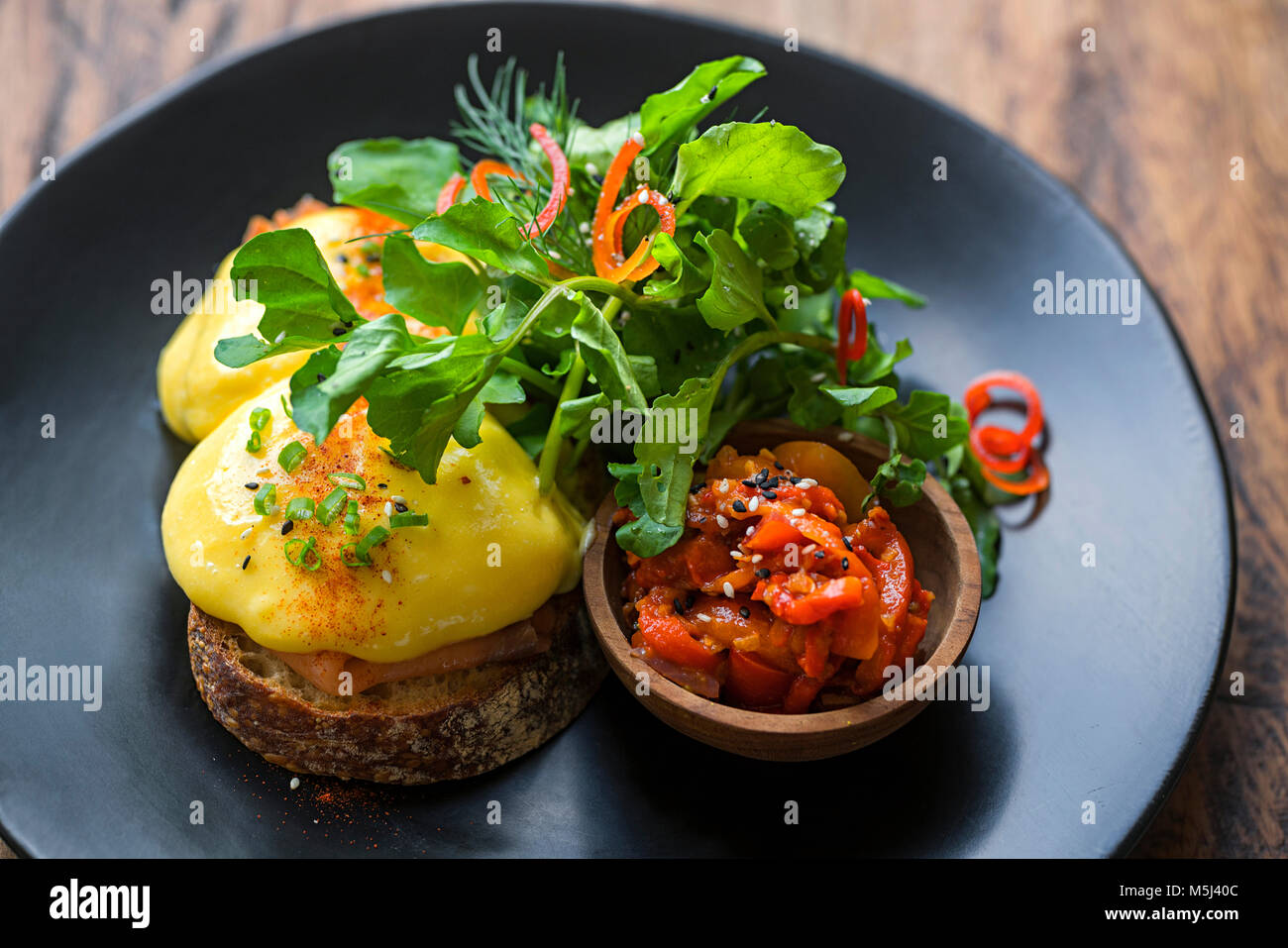 Bread gratinated with cheese with salad and vegetables on plate - Stock Image