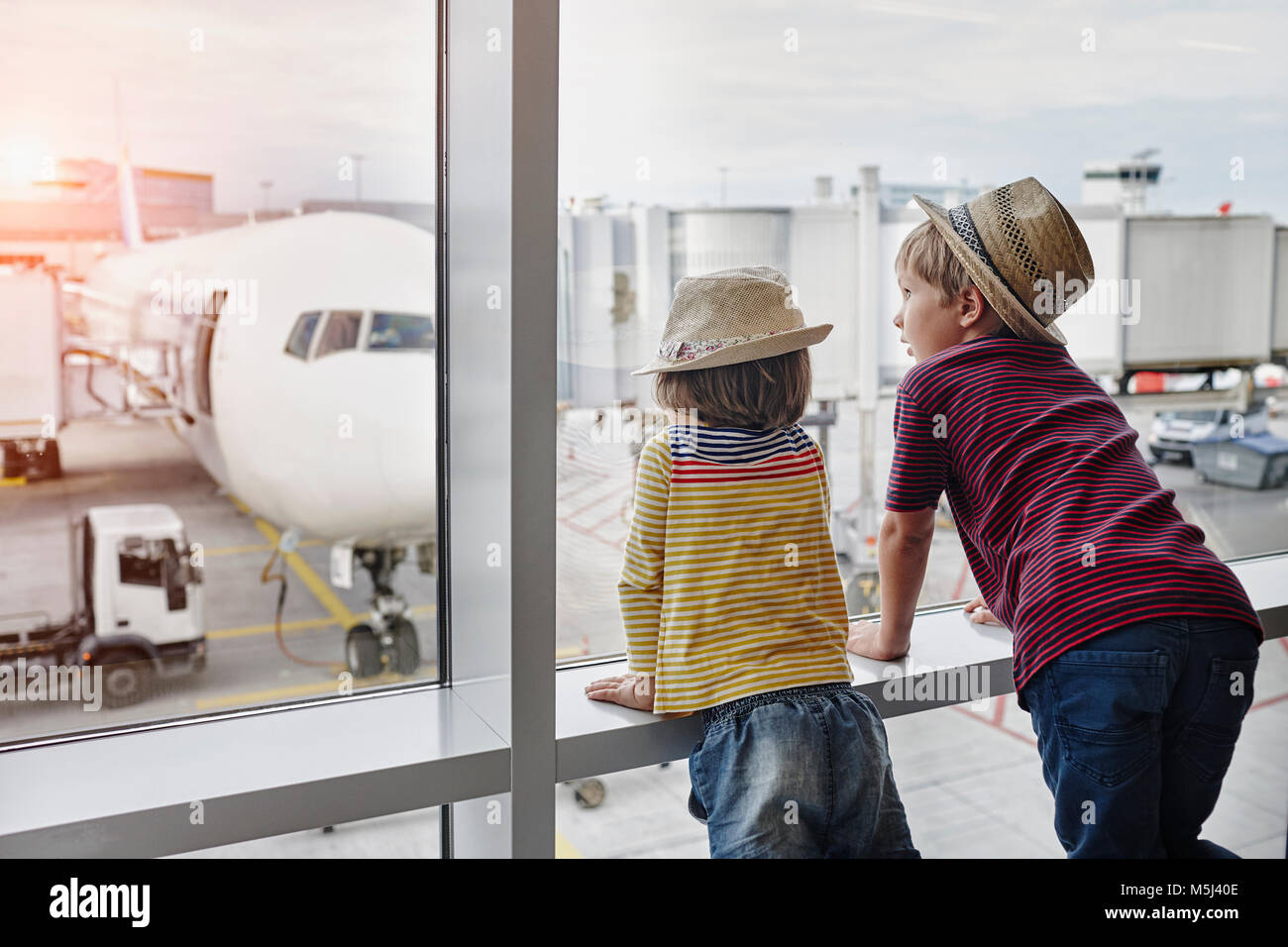 Two children wearing straw hats looking through window to airplane on the apron - Stock Image