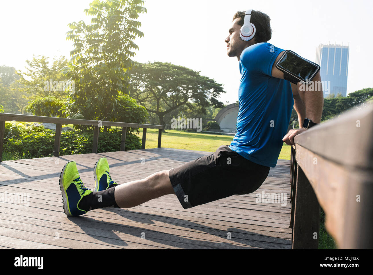 Runner with headphones doing push-ups in urban park - Stock Image
