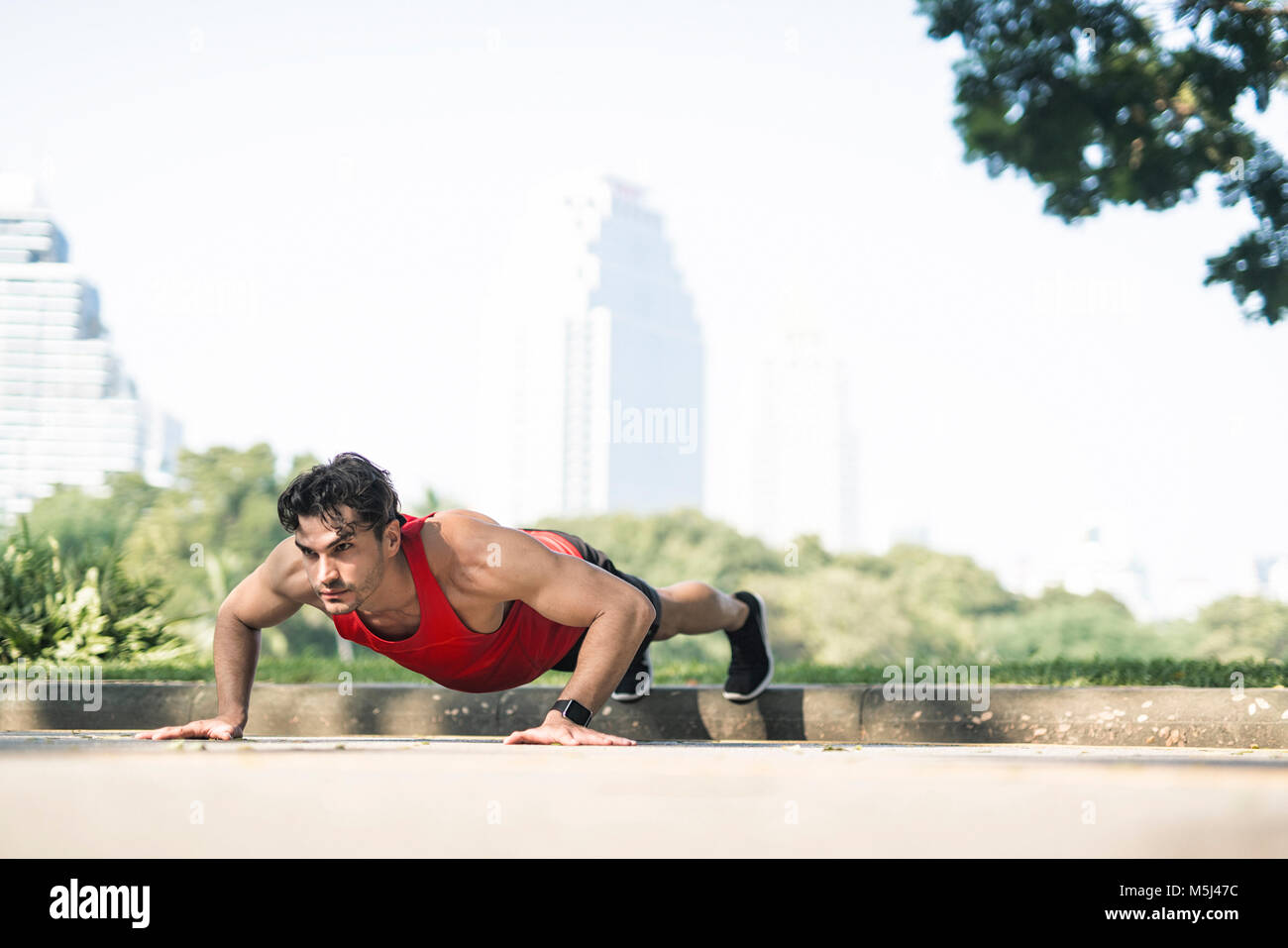 Athlete exercising push-ups in the city - Stock Image