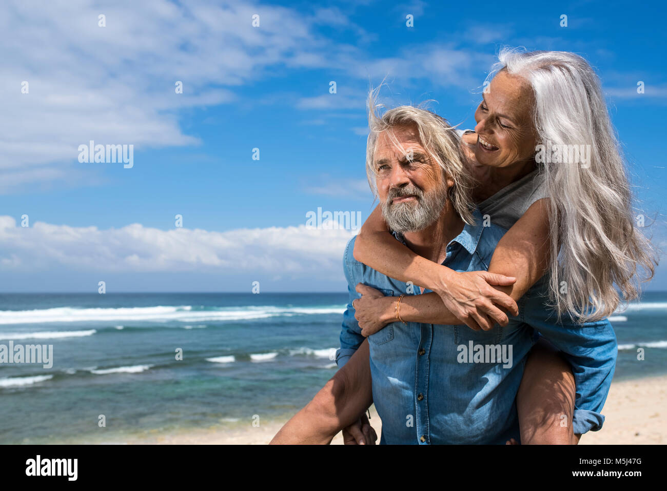 Handsome senior couple having fun at the beach - Stock Image