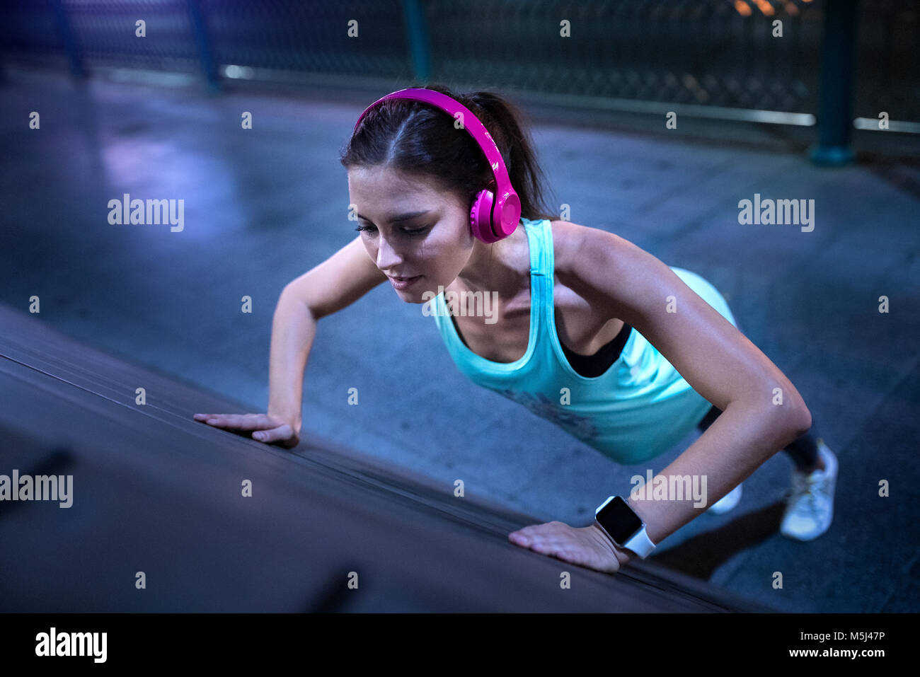 Young woman with pink headphones doing pushups in modern urban setting at night - Stock Image