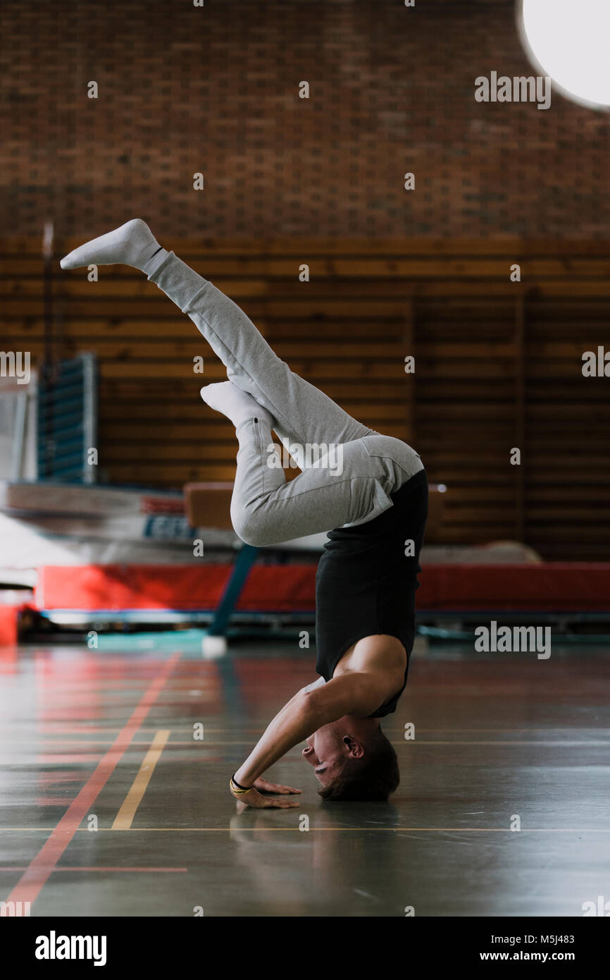 Young man doing a headstand in gym - Stock Image
