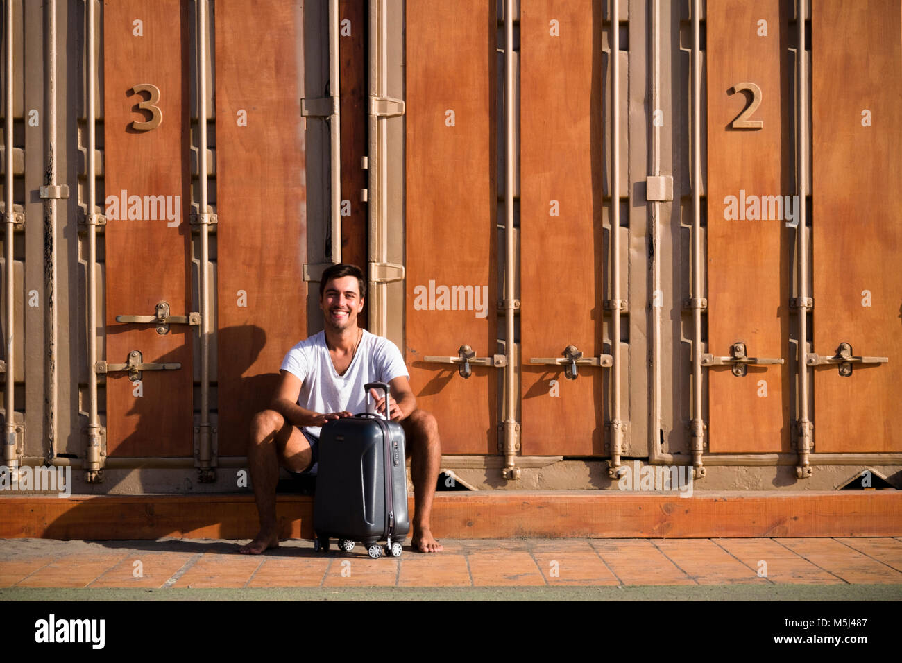 Happy man with rolling suitcase sitting in front of cubicle - Stock Image