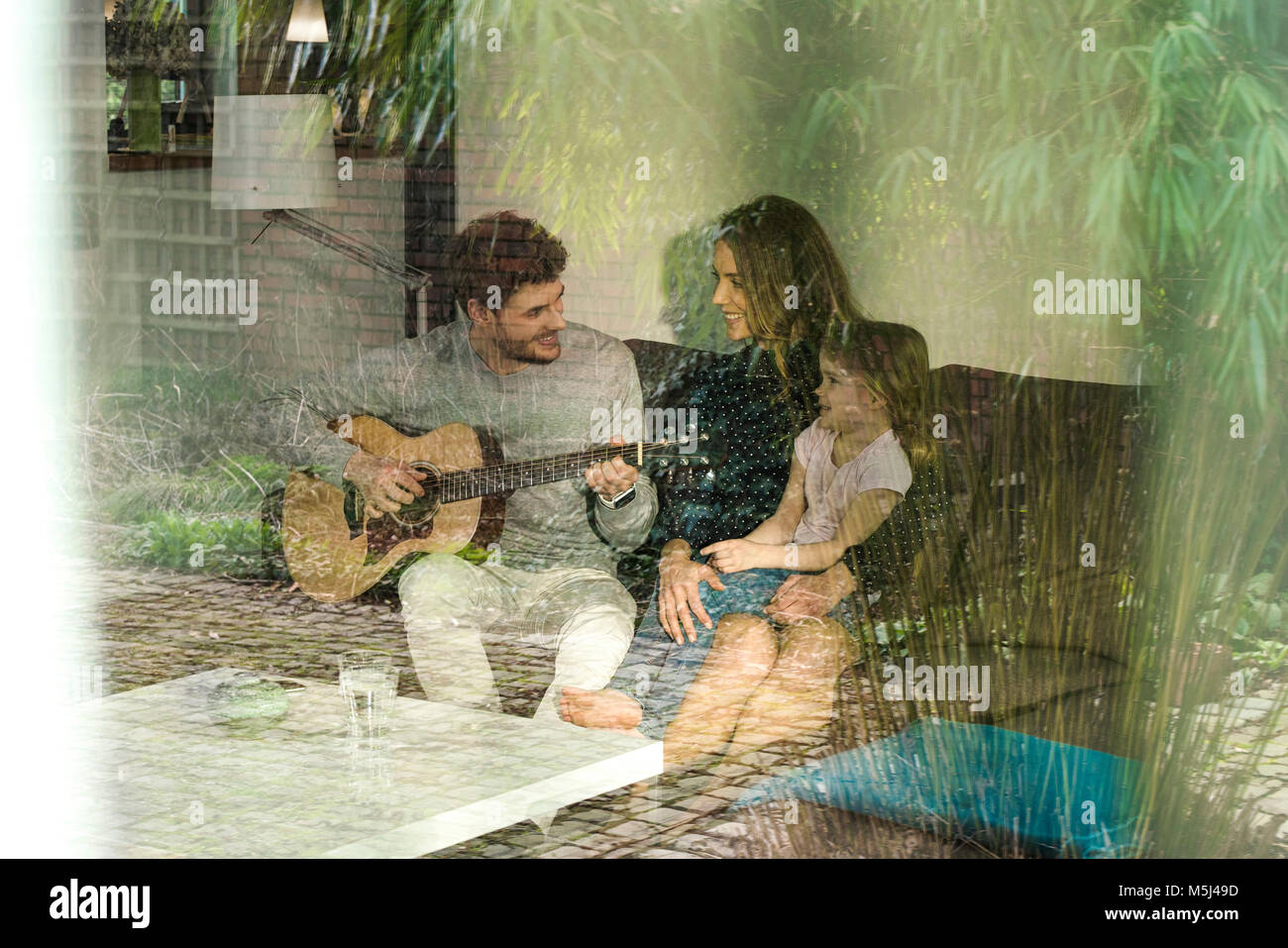 Happy parents and daughter playing guitar on sofa at home - Stock Image