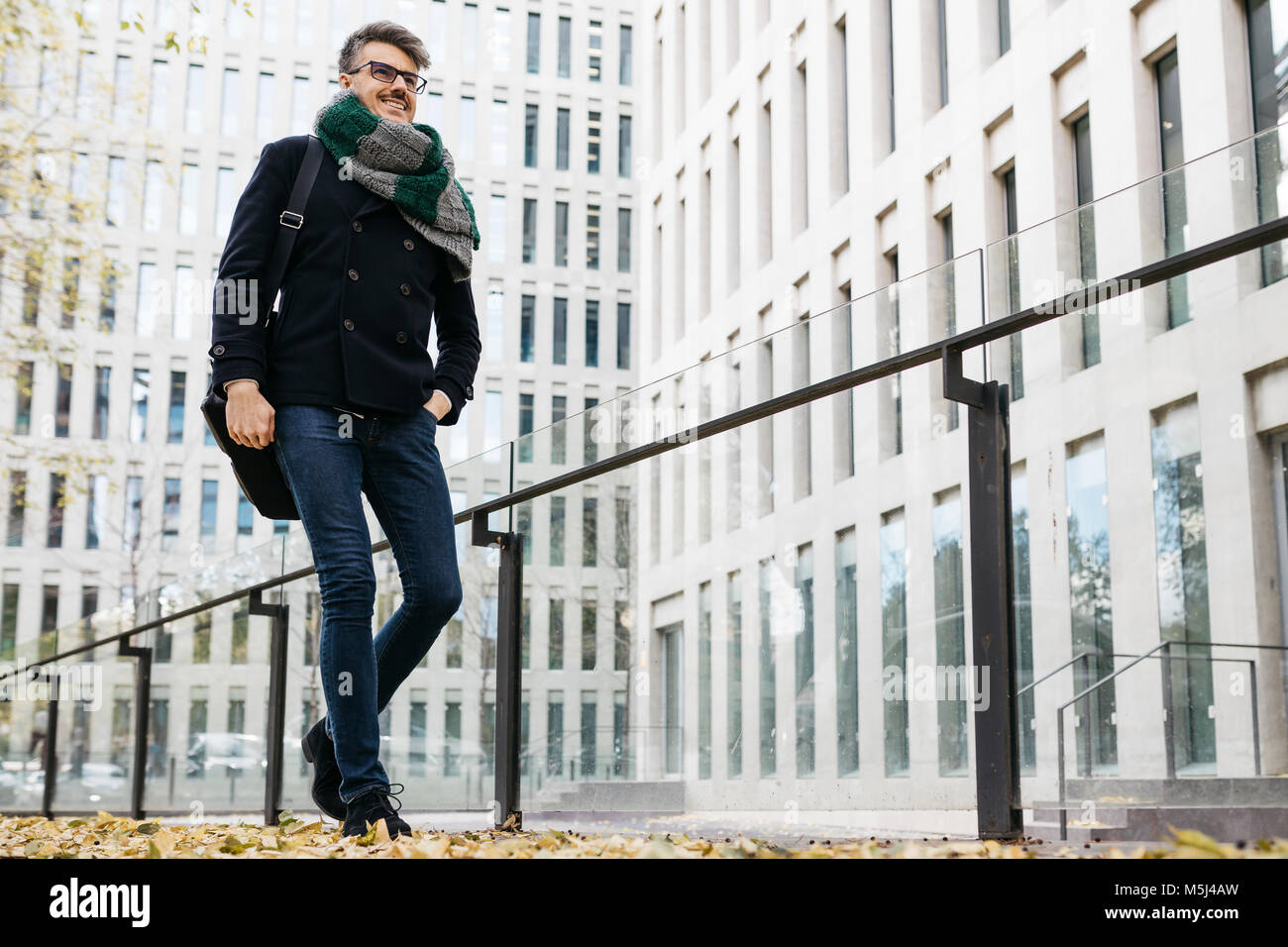 Content businessman walking in the city in autumn - Stock Image