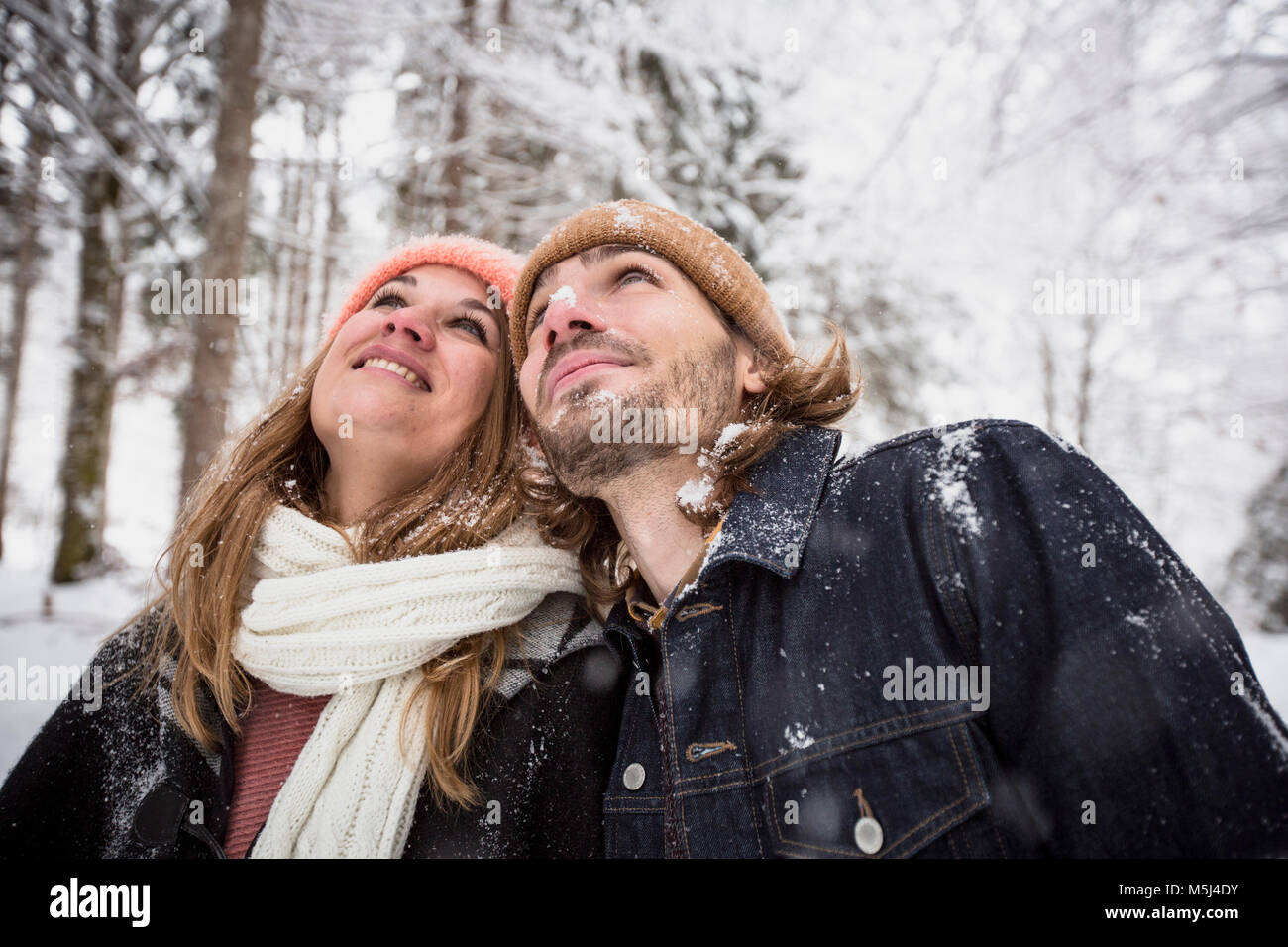 Smiling couple in winter forest watching snow fall - Stock Image