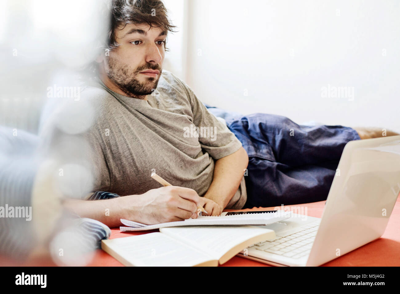 Portrait of student lying on bed with laptop and book learning - Stock Image