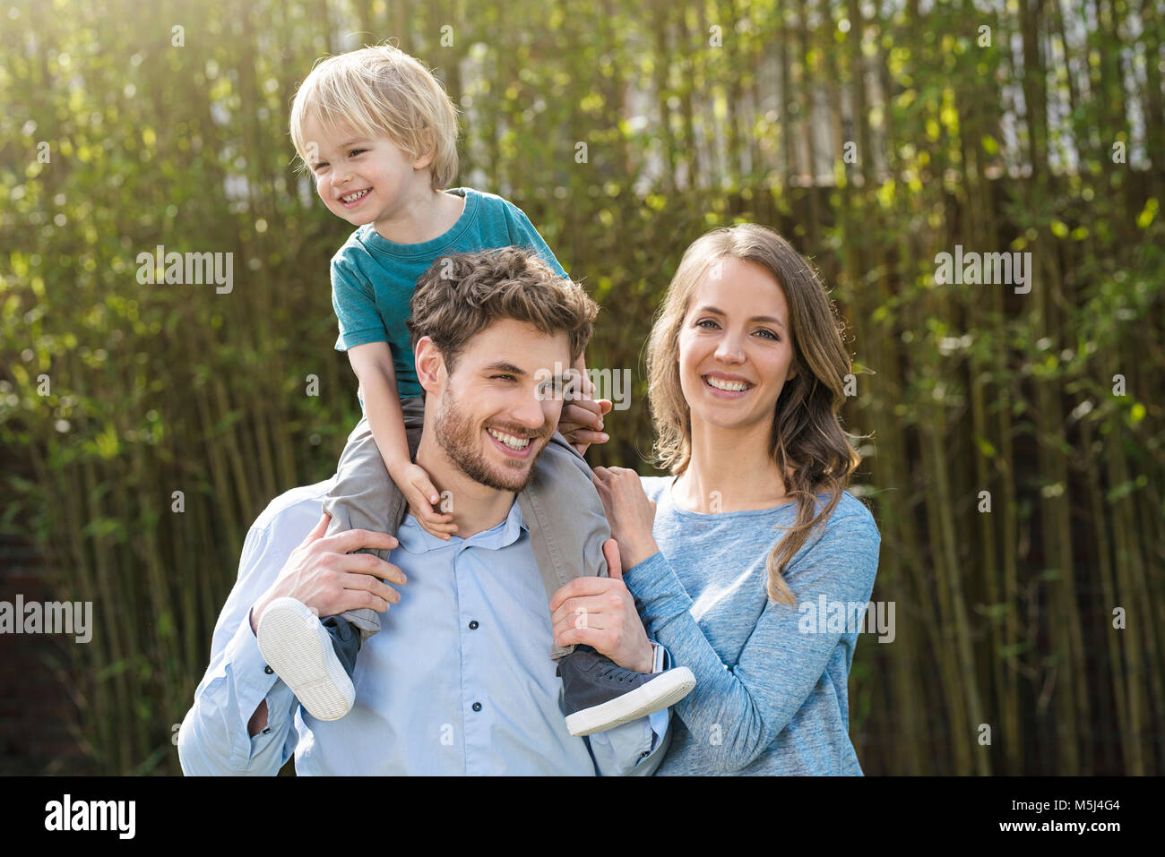 Portrait of happy family in garden in front of bamboo plants - Stock Image