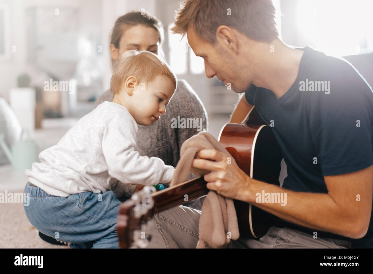 Little girl examining father's guitar at home - Stock Image