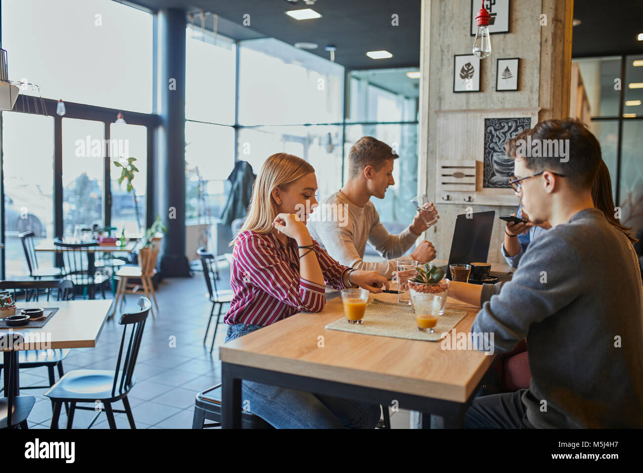 Group of friends sitting together in a cafe with laptop and drinks - Stock Image