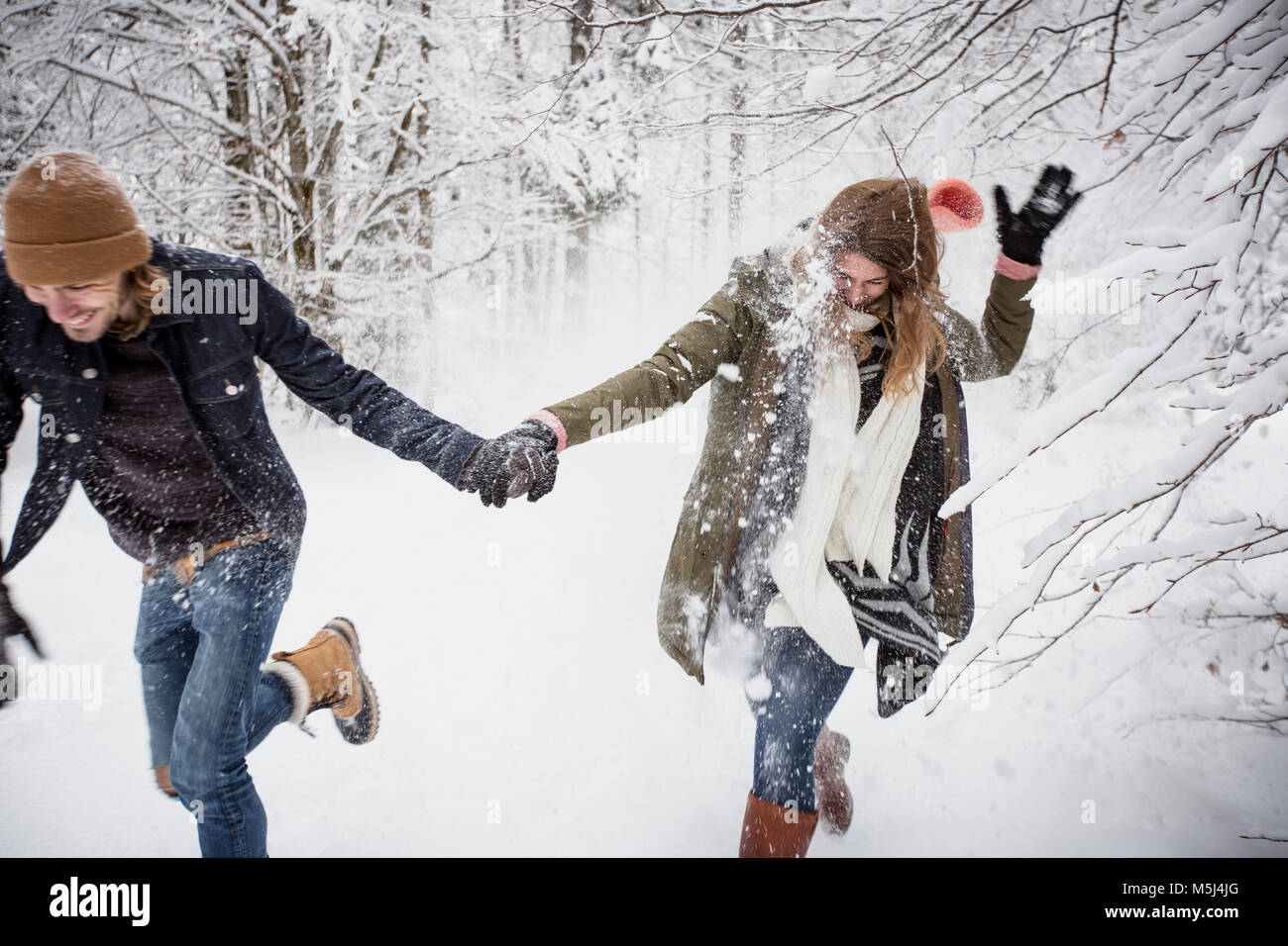 Happy couple running in winter forest - Stock Image