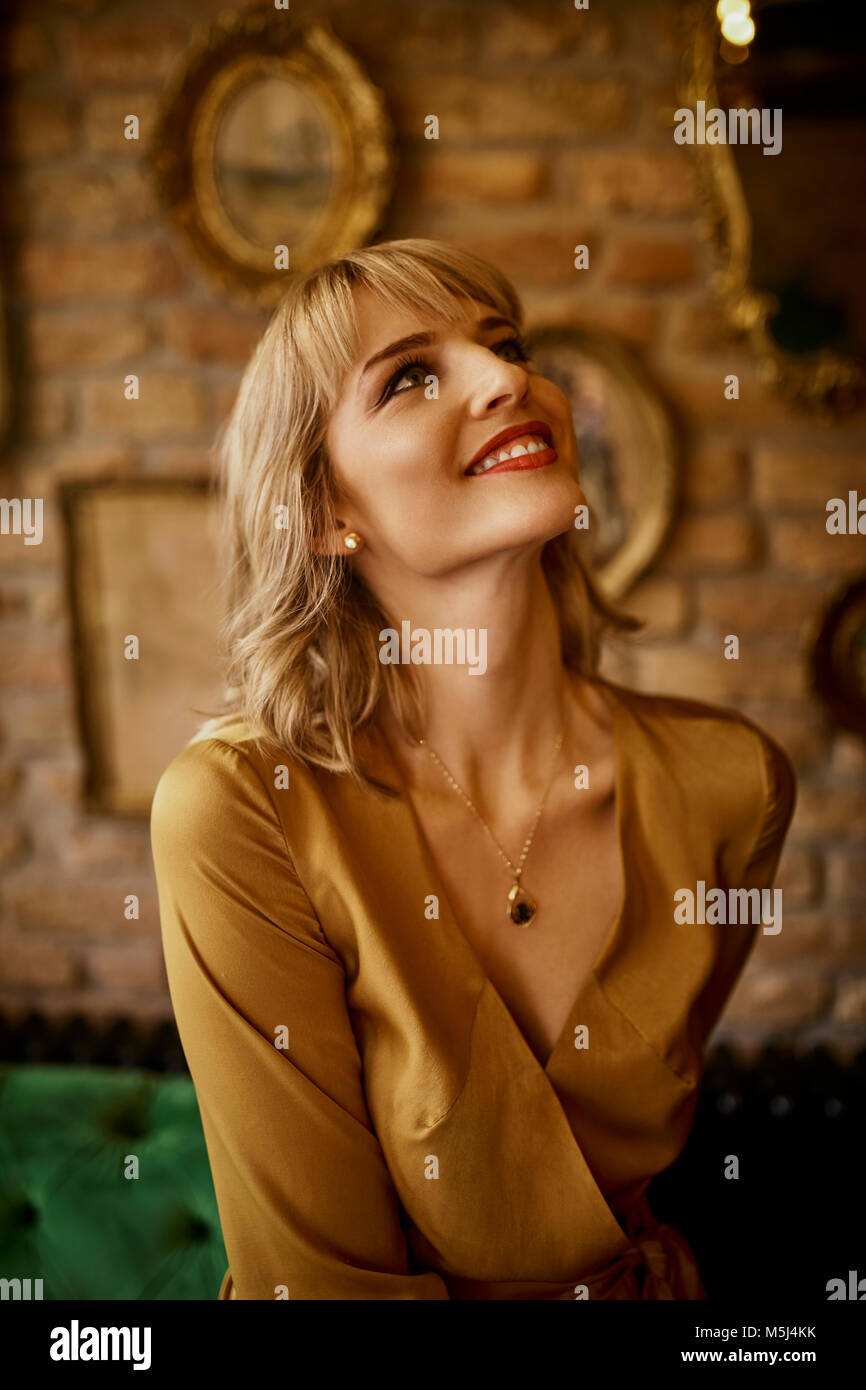 Portrait of smiling elegant woman looking up - Stock Image