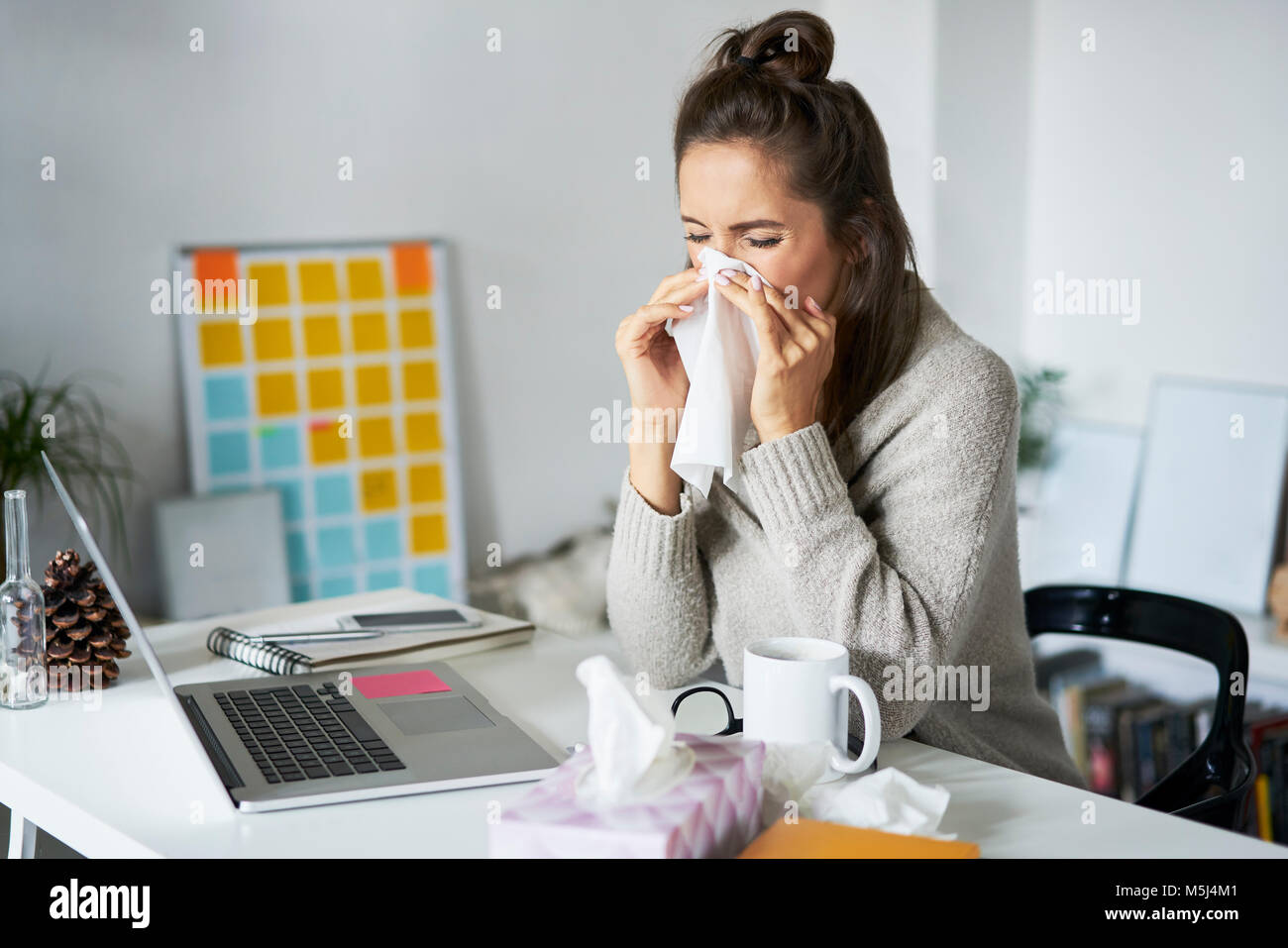 Ill woman at home at desk blowing her nose - Stock Image