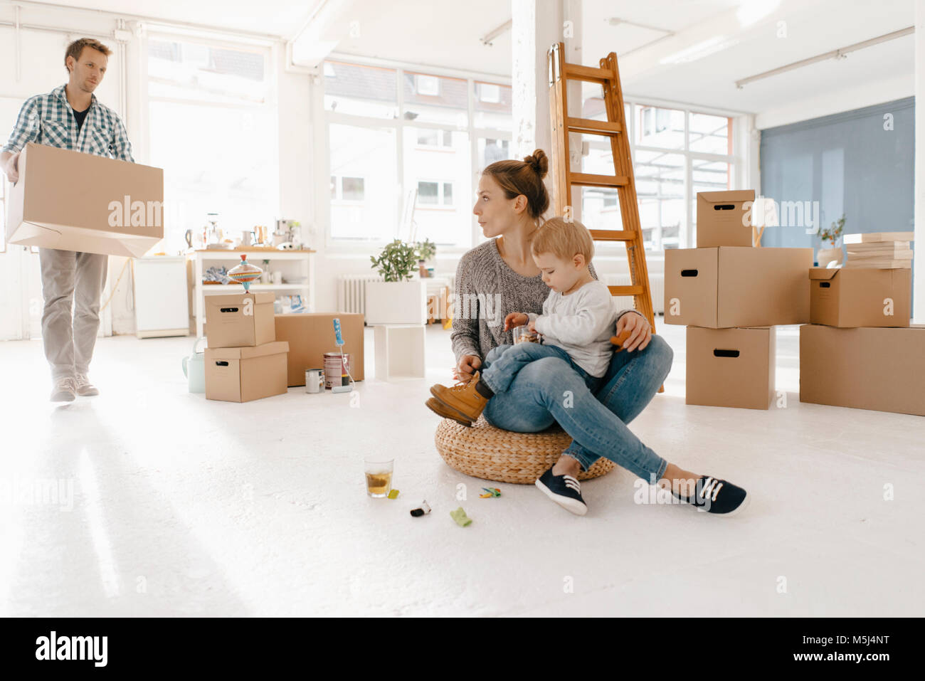 Family moving into new home with father carrying cardboard box - Stock Image