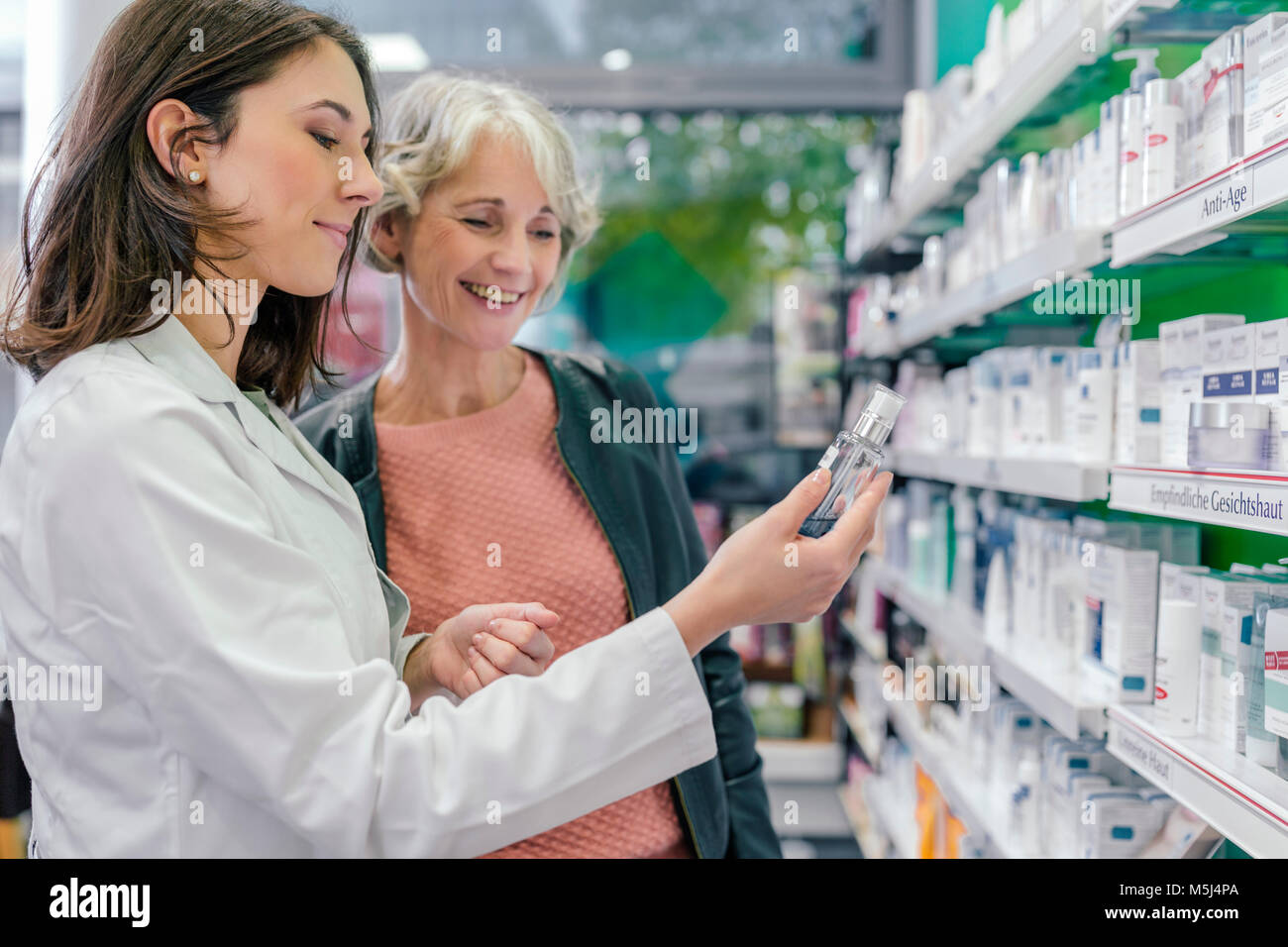 Pharmacist advising customer with cosmetics in pharmacy - Stock Image