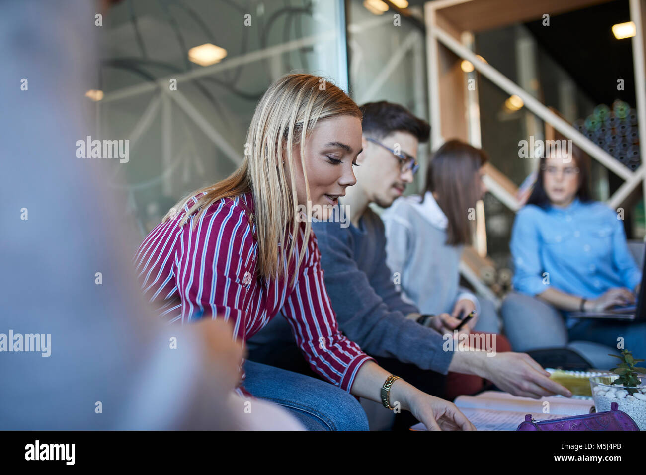 Group of friends sitting together in a cafe discussing documents - Stock Image