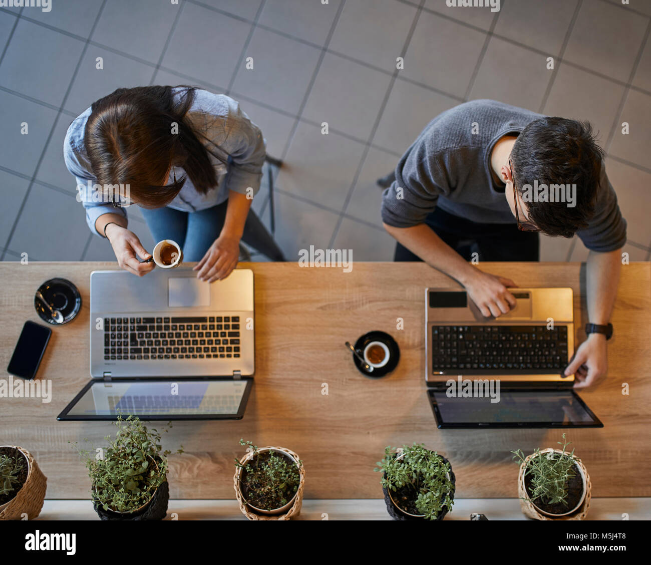 Top view of young woman and man in a cafe using laptops - Stock Image