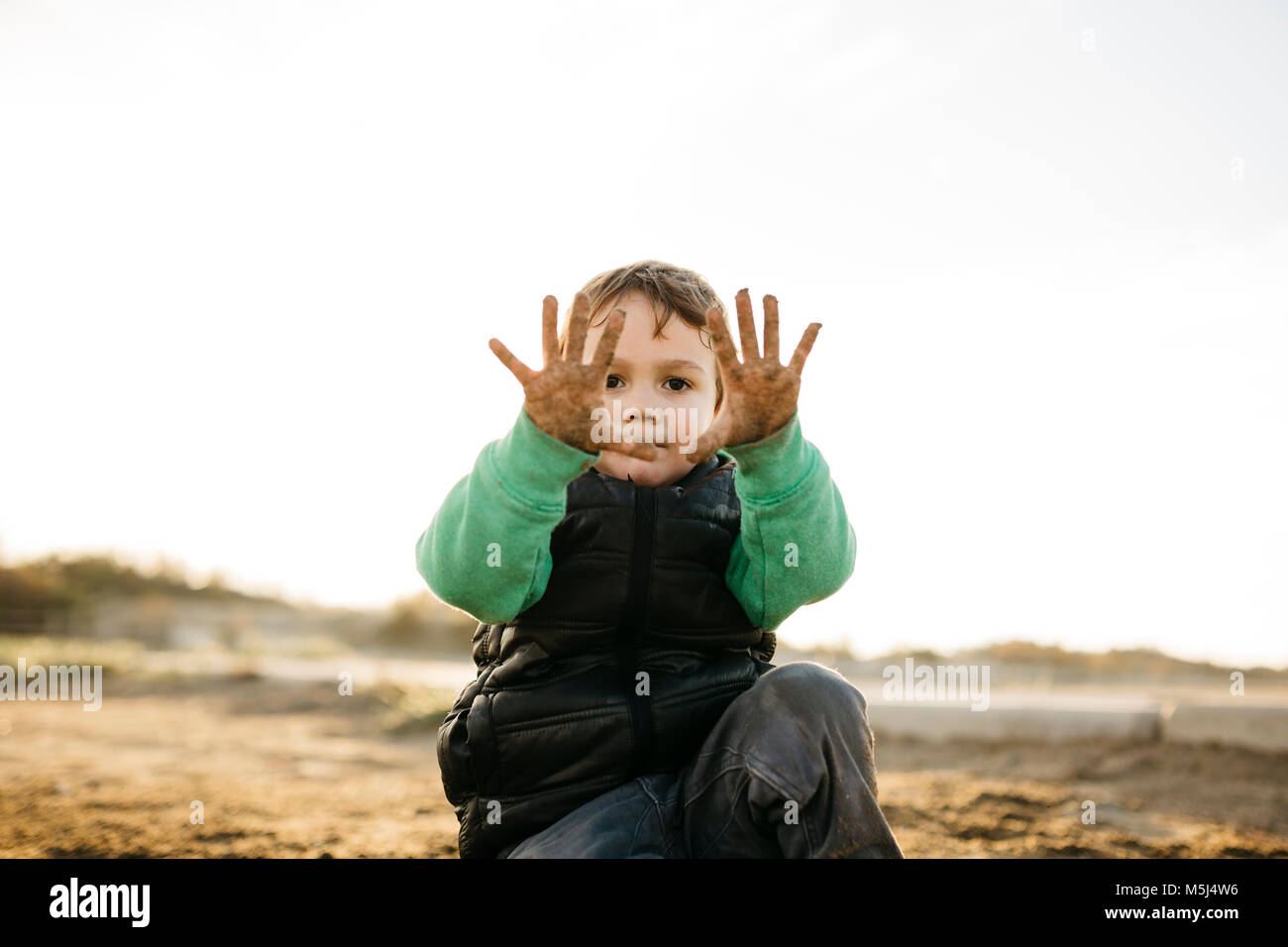 Boy playing on the beach in winter showing his dirty hands - Stock Image