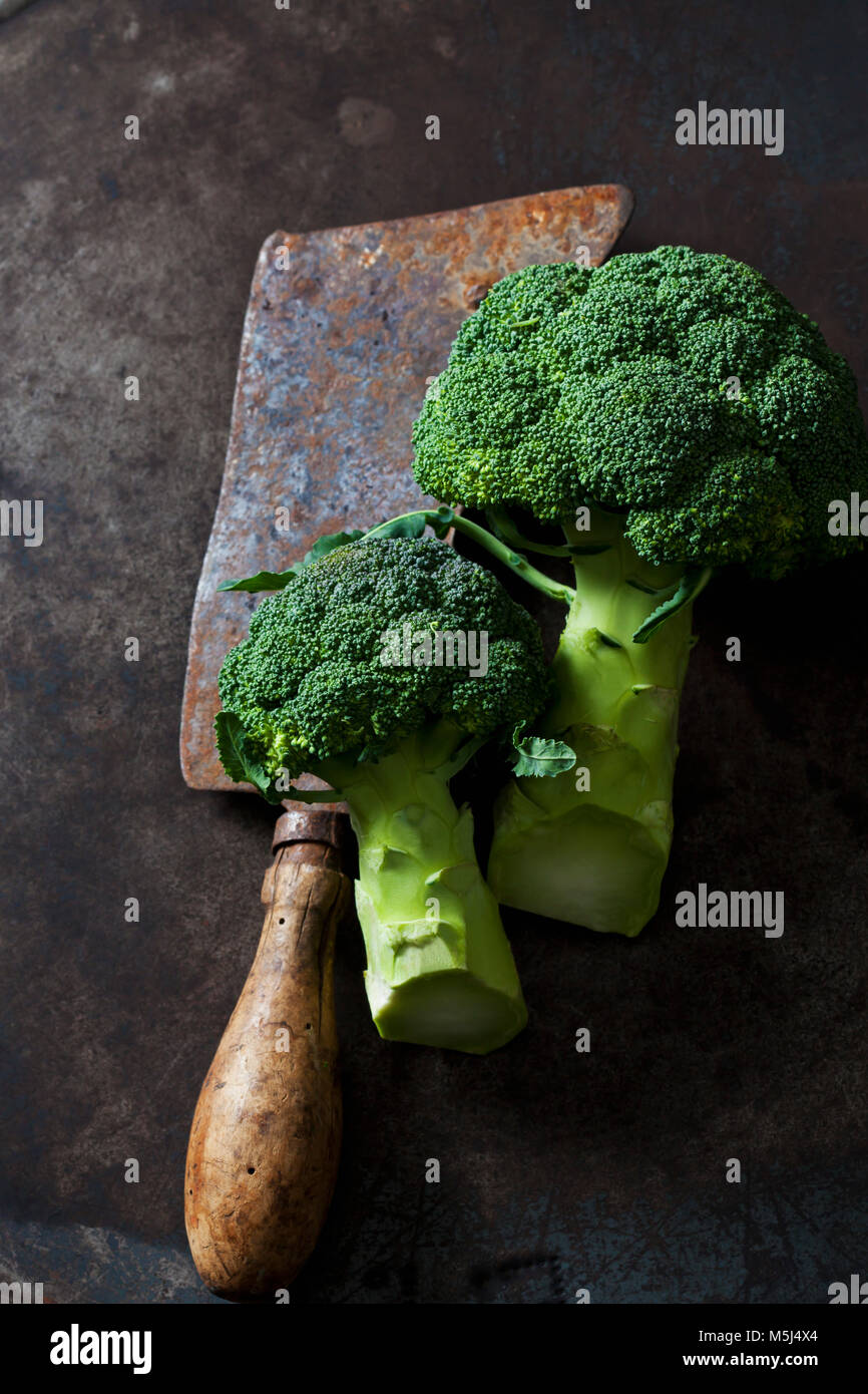 Broccoli and rusty cleaver - Stock Image