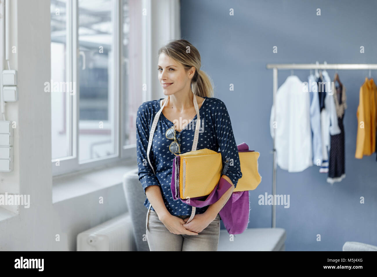 Portrait of smiling fashion designer standing in her studio - Stock Image