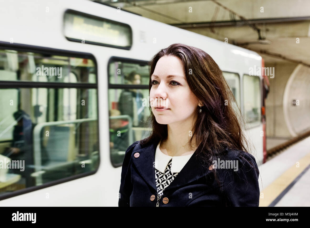 Germany, Cologne, portrait of young woman waiting at underground station platform - Stock Image
