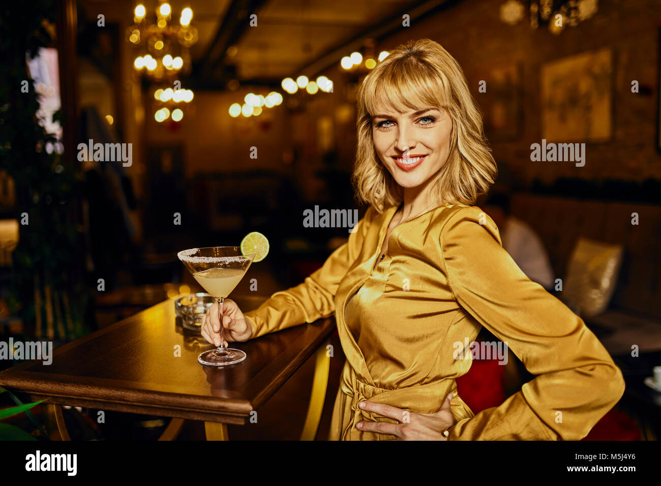 Portrait of elegant woman with cocktail in a bar - Stock Image