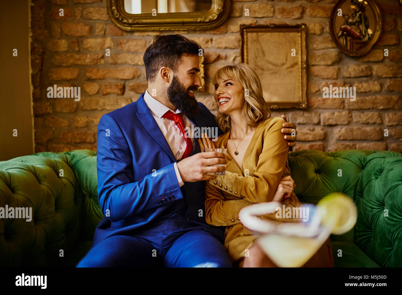 Happy elegant couple sitting on couch embracing - Stock Image
