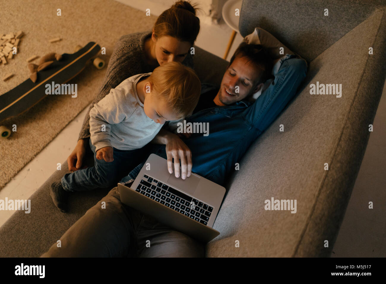 Family using laptop on the couch in the dark - Stock Image