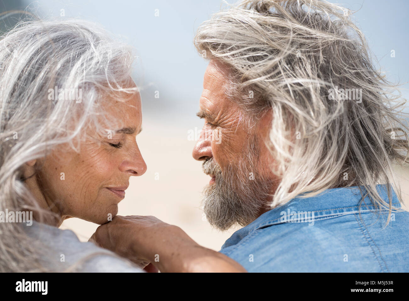 Affectionate senior couple looking into each others eyes in front of the sea - Stock Image