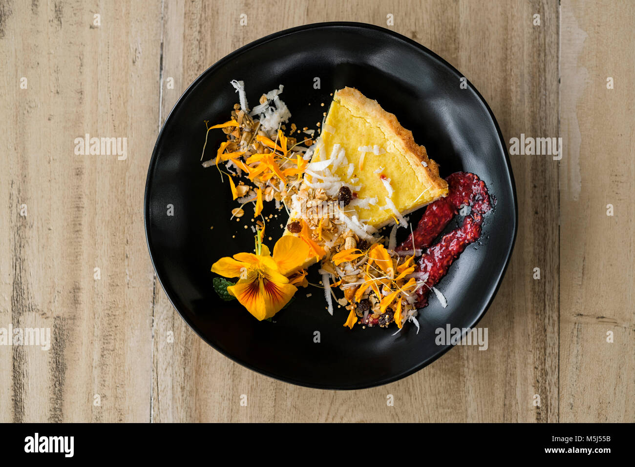 Decorated cheesecake with flowers and strawberry jam - Stock Image