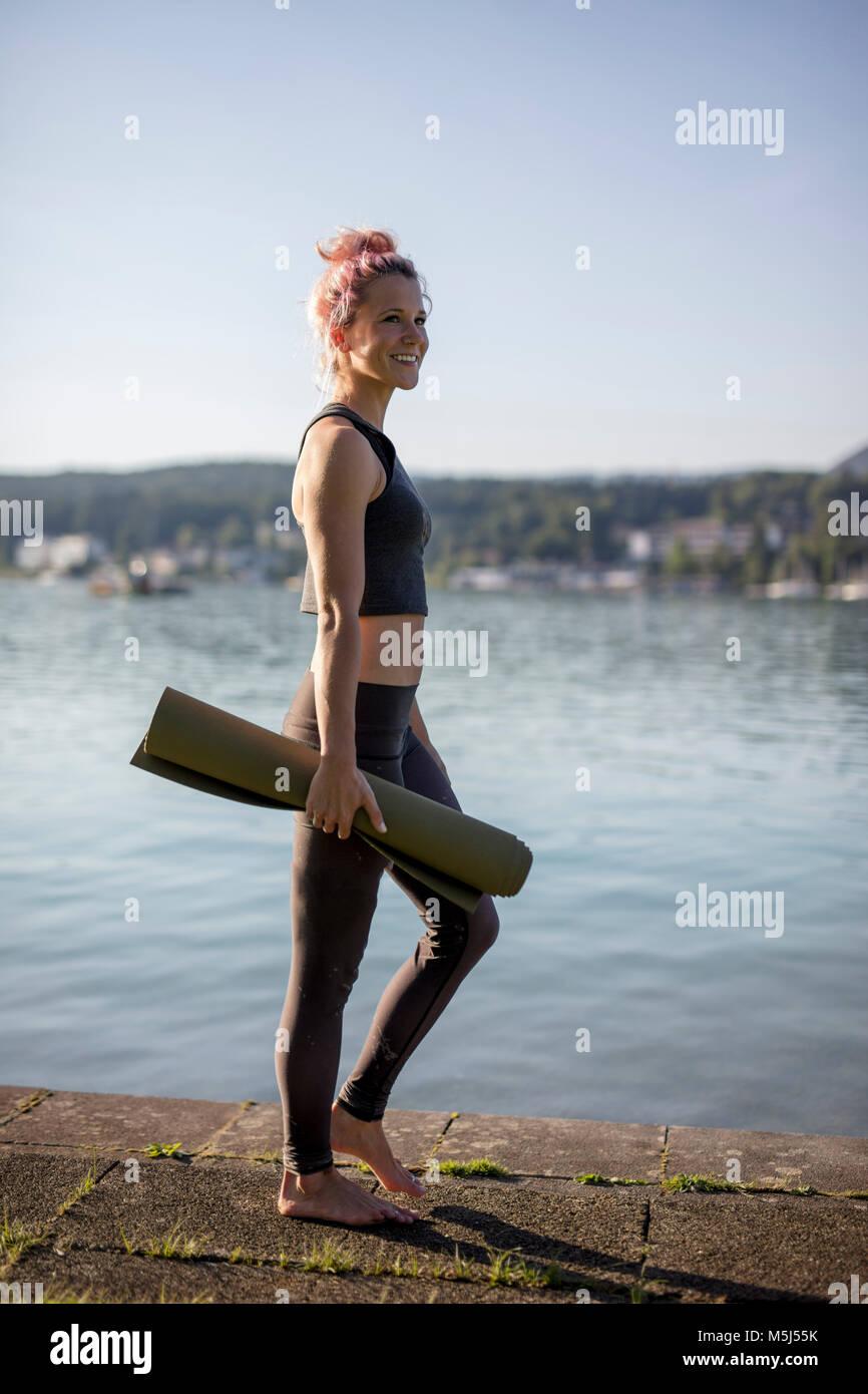 Woman in sportswear walking with yoga mat at lakeshore - Stock Image