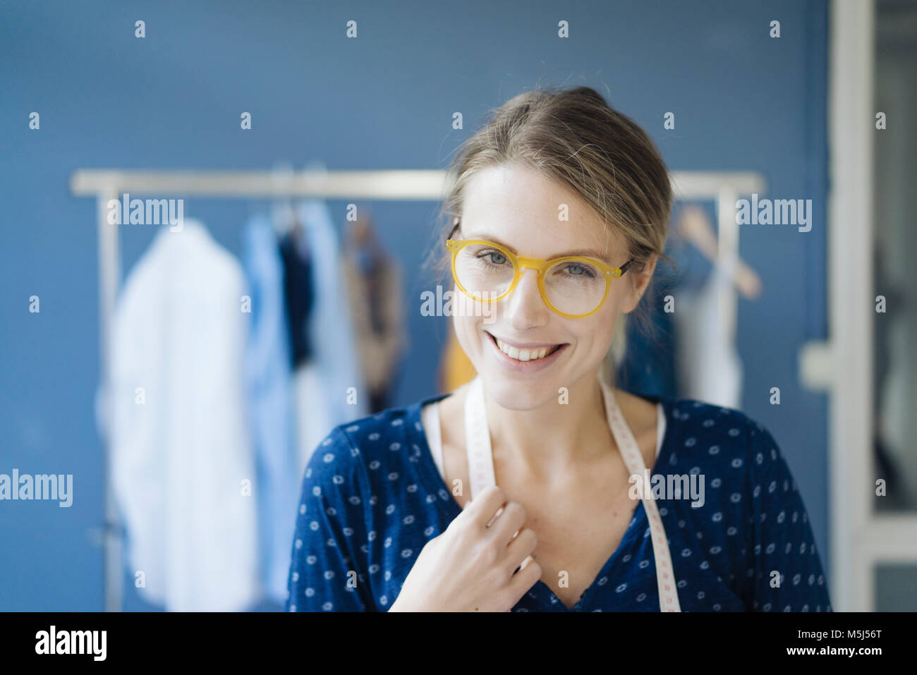 Portrait of smiling fashion designer in her studio - Stock Image