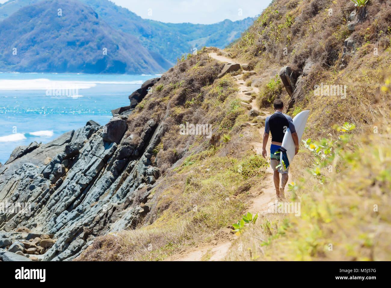 Indonesia, Lombok, surfer walking at ocean coastline - Stock Image