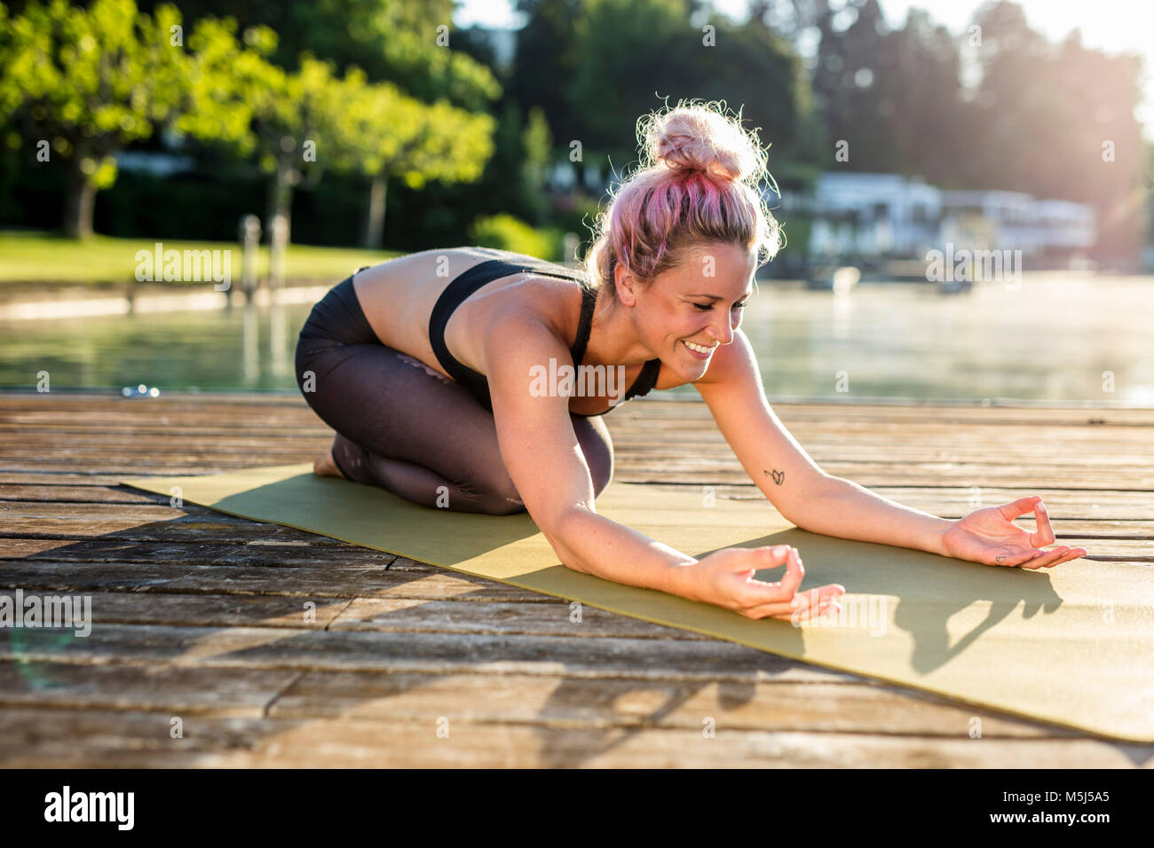 Smiling woman practicing yoga on jetty at a lake - Stock Image