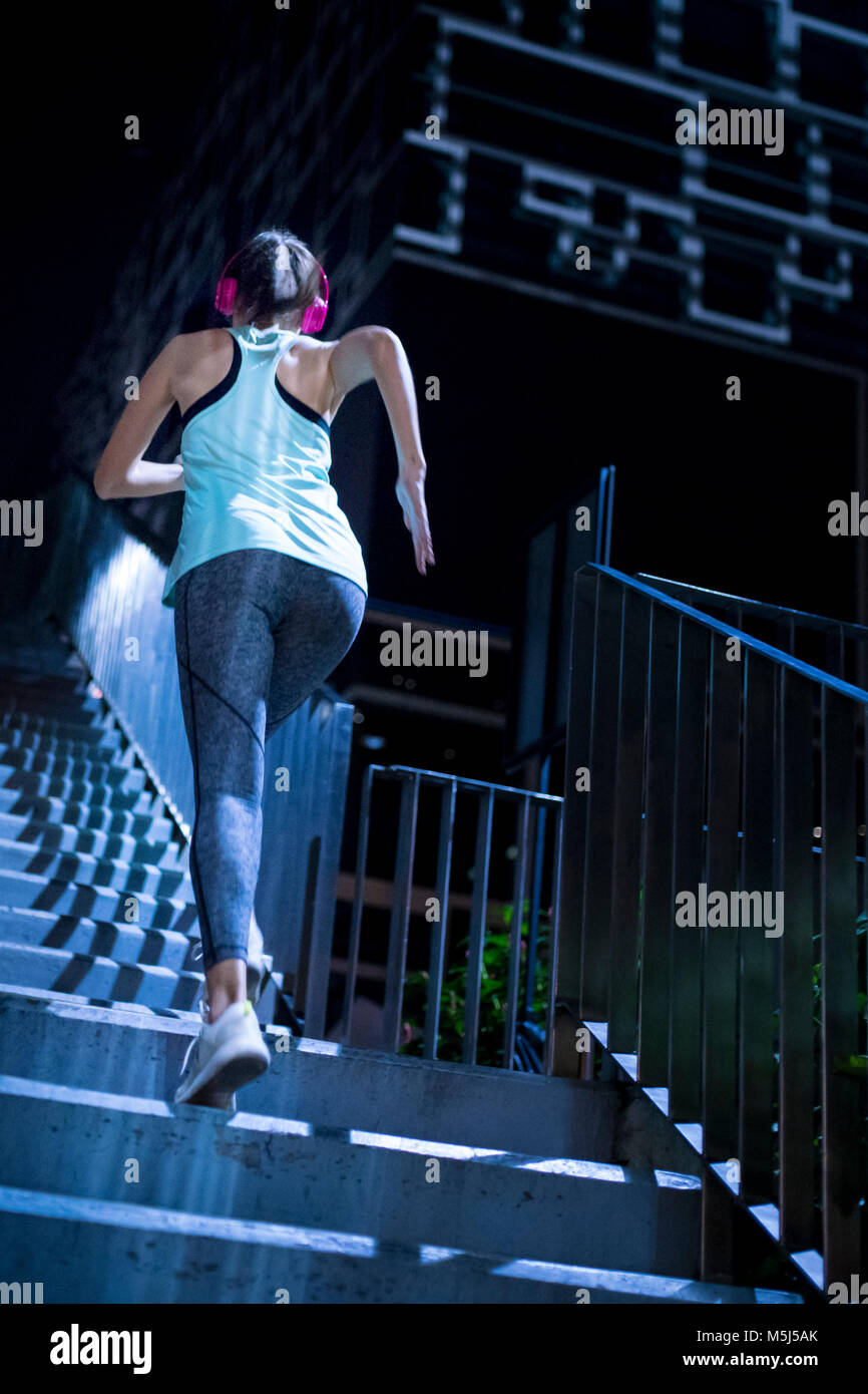 Young woman with pink headphones running upstairs in modern urban setting at night - Stock Image