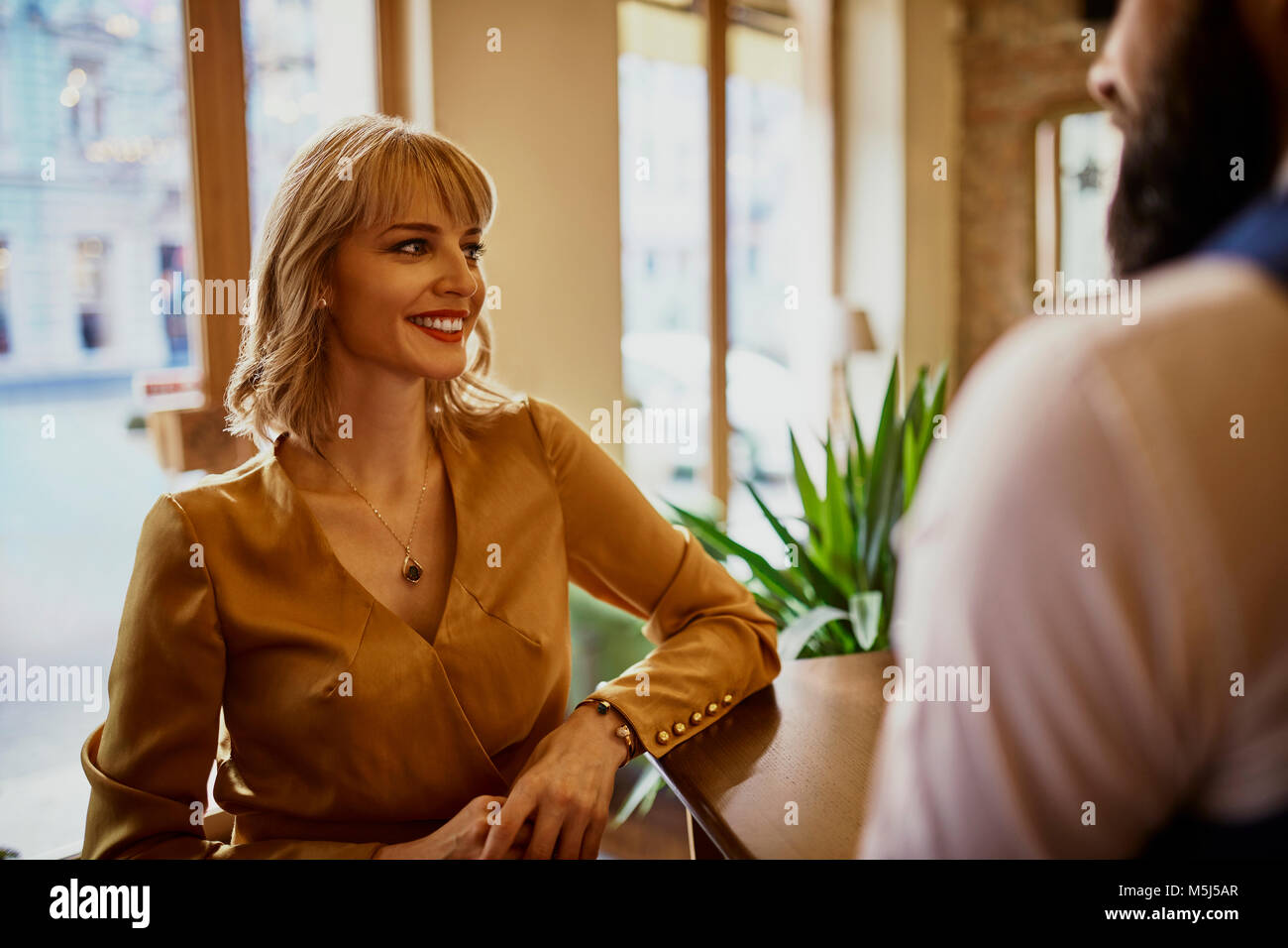 Elegant smiling woman with man in a bar - Stock Image